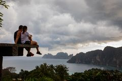 Piękny pary obsiadanie na drewnianej platformie z Phi Phi wyspy widokami i chmurnym niebem obraz stock