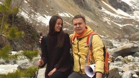 Piękny pary obsiadanie na kamieniu w górach i podziwia scenerię zbiory