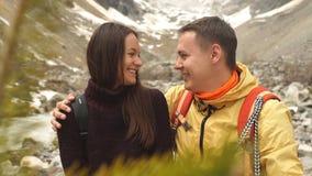 Piękny pary obsiadanie na kamieniu w górach i podziwia scenerię zbiory wideo
