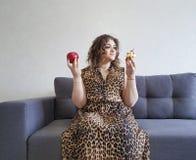Piękny pełny dziewczyna kędzierzawego włosy jabłko i tort, ładna wyrażeniowa wyborowa emoci kanapa zdjęcie stock