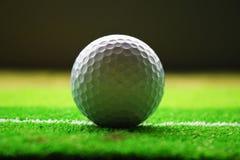 Piękny piłki golfowej zakończenie up na zielonej teksturze Zdjęcia Stock