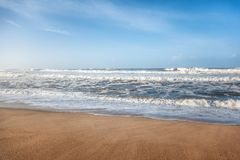Piękny piaskowaty oceanu wybrzeże, fala i niebieskie niebo, Obraz Royalty Free