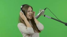 Piękny piosenkarz jest bardzo ekspresyjny śpiewa w pracownianym mikrofonie Na zielonym tle zbiory wideo