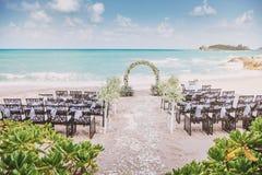 Piękny plażowego ślubu miejsca wydarzenia położenie z kwiatami, kwiecista dekoracja na łuku, panoramiczny widok na ocean fotografia royalty free