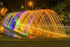 Piękny plenerowy widok kolorowa wodna rozrywki struktury fontanna przy długim ujawnieniem w nocy z budynkami, obraz stock