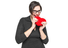 Piękny plus wielkościowa kobieta gryźć czerwonego serce odizolowywającego Fotografia Royalty Free