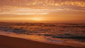 Piękny pomarańczowy niebo z chmurami nad oceanem przy zmierzchem na plaży fotografia royalty free