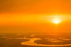 Piękny pomarańczowy zmierzch nad rzeką, chwytającą od samolotu Obrazy Stock