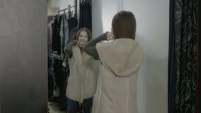 Piękny popularny kobieta zakupy próbować odziewa w trafnym pokoju i patrzeć w lustrze - zbiory wideo