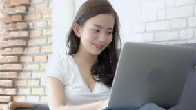 Piękny portret azjatykcia młoda kobieta excited i uradowana sukces z laptopem na kanapa cementu tle zbiory
