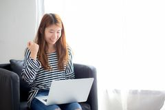 Piękny portret azjatykcia młoda kobieta excited i uradowana sukces z laptopem na krześle przy sypialnią obrazy royalty free