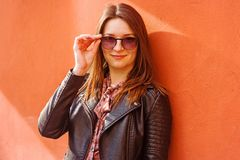 Piękny portret brunetki kobieta przeciw ścianie w słonecznym dniu zdjęcia royalty free