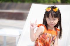 Piękny portret małej dziewczynki azjata uśmiechnięty obsiadanie przy pływackim basenem Fotografia Stock