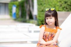 Piękny portret małej dziewczynki azjata uśmiechnięty obsiadanie przy pływackim basenem Obrazy Royalty Free