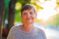 Piękny portret uśmiechać się starzejącej się kobiety na lato ulicie Kaukaska babcia patrzeje kamerę fotografia royalty free
