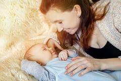 Piękny, potomstwo matki spojrzenia przy uśmiechniętym dzieckiem sunlight obrazy stock