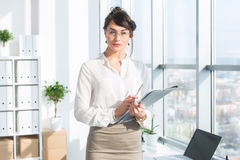Piękny, poważny konsultant jest ubranym szkła, i formalny biurowy kostium, trzymający jej pracę stacjonarna, patrzejący kamerę zdjęcie royalty free