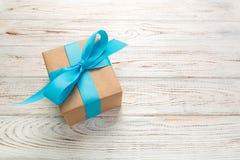 Piękny prezenta pudełko z błękitnym łękiem na białym drewnianym stole Odgórny widok obrazy royalty free