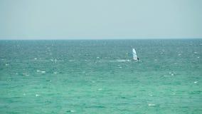 Piękny seascape z osamotnionym surfingowem jedzie surfboard na niebieskiego nieba tle, sporta pojęcie strza? pla?y ?wietnie piask zdjęcie wideo