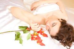 Piękny seksowny kobiety lying on the beach w łóżkowym i patrzeć płatki Zdjęcia Royalty Free