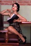 Piękny seksowny młodej kobiety obsiadanie przy cukiernianym stołem z książką fotografia royalty free