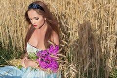 Piękny sexualintelligance dziewczyny model w błękit sukni z różowym warga projektem demonstruje obręcz na głowie w polu na Pogodn Zdjęcie Stock