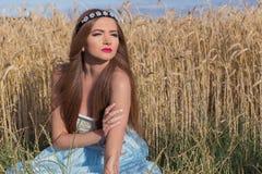 Piękny sexualintelligance dziewczyny model w błękit sukni z różowym warga projektem demonstruje obręcz na głowie w polu na Pogodn Fotografia Royalty Free