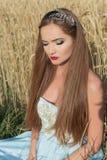 Piękny sexualintelligance dziewczyny model w błękit sukni z różowym warga projektem demonstruje obręcz na głowie w polu na Pogodn Fotografia Stock