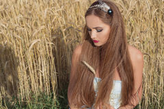 Piękny sexualintelligance dziewczyny model w błękit sukni z różowym warga projektem demonstruje obręcz na głowie w polu na Pogodn Zdjęcie Royalty Free