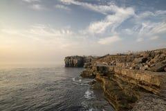 Piękny skalisty faleza krajobraz z zmierzchem nad oceanem Fotografia Royalty Free