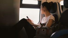 Piękny spokojny Kaukaski żeński dojeżdżający sprawdza smartphone app podróżuje w taborowym samochodzie, patrzeje okno zbiory wideo