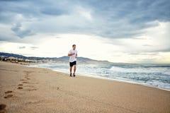 Piękny sportowy sportowa bieg wzdłuż plaży na zadziwiającym morza i nieba tle Obraz Stock