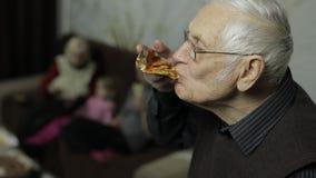 Piękny starsza osoba mężczyzna w szkłach je pizzę Jego rodzina w tle zbiory