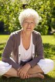 Piękny starszy kobiety obsiadanie w jej ogródzie zdjęcie stock