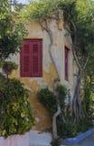 Piękny stary dom z czerwieni żaluzjami, otaczać zielonym bushe Zdjęcia Stock