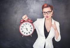 Piękny surowy nauczyciel z zegarem na blackboard tle fotografia stock