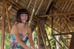 Piękny szczęśliwy młodej dziewczyny obsiadanie w drewnianym gazebo przy słonecznym dniem Tropikalna Bali wyspa, Indonezja Zdjęcie Stock