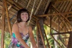 Piękny szczęśliwy młodej dziewczyny obsiadanie w drewnianym gazebo przy słonecznym dniem Tropikalna Bali wyspa, Indonezja Obrazy Stock