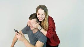 Piękny szczęśliwy uśmiechnięty kobiety nakrycie ono przygląda się z jej rękami przystojny młody człowiek w zabawa nastroju zdjęcie royalty free