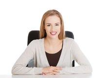 Piękny szczęśliwy, uśmiechnięty kobiety obsiadanie biurkiem, obraz royalty free