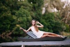 Piękny szczupły modny dziewczyny lying on the beach w pokładu krześle blisko rzeki 20 piękna wieka wystawy retrospektywnej przegl Zdjęcie Stock