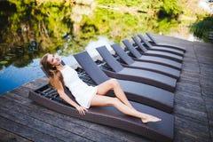 Piękny szczupły modny dziewczyny lying on the beach w pokładu krześle blisko rzeki 20 piękna wieka wystawy retrospektywnej przegl Zdjęcia Royalty Free