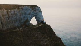 Piękny trutnia panning widok szczęśliwi przyjaciele wpólnie ogląda zmierzchu morze na górze Normandy brzeg falezy dobiera się obs zbiory wideo