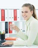 Piękny uśmiechnięty bizneswoman trzyma szkło woda w ręce podczas gdy pracujący na komputerze przy biurem Zdjęcie Stock