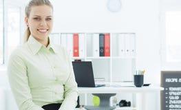 Piękny uśmiechnięty bizneswomanu obsiadanie na tle jej biuro Obrazy Stock