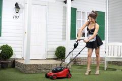Piękny uśmiechnięty housemaid kosi gazon kosiarzem zdjęcia stock