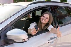 Piękny uśmiechnięty kobieta seansu klucz od samochodu przez okno zdjęcie royalty free