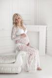 Piękny uśmiechnięty kobieta w ciąży w koronki sukni obsiadaniu na kanapie, Fotografia Royalty Free