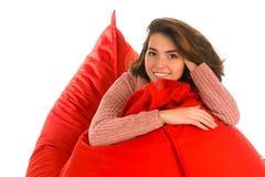 Piękny uśmiechnięty kobiety obsiadanie na czerwonym beanbag kanapy krzesła pokoju ja Fotografia Royalty Free