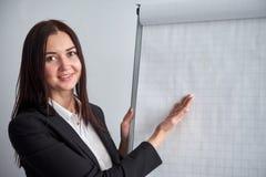 Piękny uśmiechnięty młodej kobiety writing na pustym flipchart w biurze gdy robi promoci lub prezentaci obraz stock